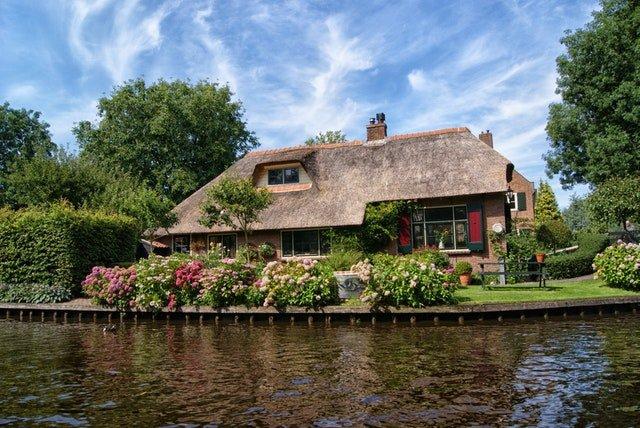 Rodinný dom v hnedých farbách postavený priamo pri vode.jpg