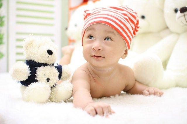 Bábätko v červeno-bielej čiapke lezie v postieľke a vedľa má plyšovú hračku