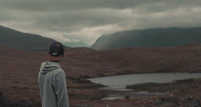 Muž stojí v údolí a pozerá sa do diaľky